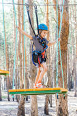 Little girl climbs on rope harness — Stock Photo