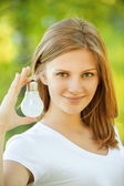 Smiling woman shows incandescent lamp — Stock Photo