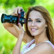 Beautiful woman holds camera — Stock Photo
