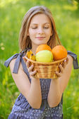 Portrait of woman holding basket with fruits — Stock Photo