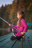 Little girl catches fishing rod — Stock Photo