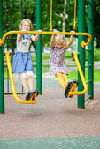 Two girls swinging on playground — Photo