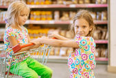 Little beautiful sisters in supermarket — Stockfoto