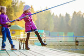 Little girls catches fishing rod — Stock Photo