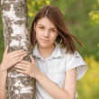 Portrait of young dark-haired woman embracing birch tree — Stock Photo #49090389