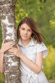 Portrait of young dark-haired woman embracing birch tree — Stock Photo