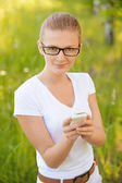Portrait of young fair-haired woman looking at mobile phone — Stock Photo