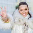 Girl in fur coat shows victory — Stock Photo #49396645
