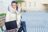 Woman in white coat sitting on bench — Stock Photo