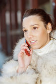 Smiling woman in white coat talking on phone — Stock Photo
