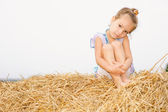 Little girl on haystack. — Stock Photo