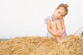Little girl on haystack. — Stock Photo