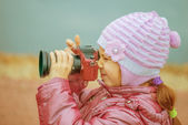 Little girl in with red camera photographs — Stock Photo