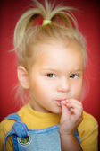 Little girl with finger on mouth — Stock Photo