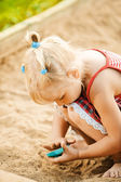 Little blonde girl playing in sandpit — Stock Photo