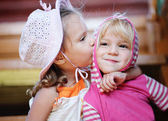 Little girl kisses sister. — Stock Photo