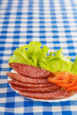 Sliced smoked sausage, tomatoes, lettuce — Stock Photo