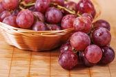 натюрморт: плетеная корзина с виноградом в плетеный — Стоковое фото