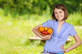 Portrait of young smiling brunette holding basket with fruits — Stock Photo