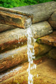 Wooden trough on holy spring — Stock Photo