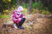 Little girl on stump — Stock Photo