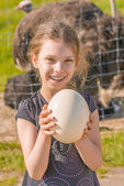 Smiling girl holding ostrich egg — Stock Photo