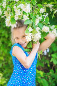 Smiling girl near blooming jasmine — Stock Photo