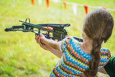 Little girl shooting crossbow — Stock Photo