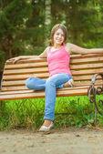 Niña sentada en el banco — Foto de Stock