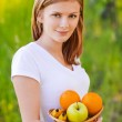 Portrait of woman holding basket with fruits — Stock Photo #6145559