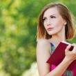 Serious young beautiful woman holding red book — Stock Photo #7763817