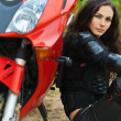 Portrait beautiful young woman leaning motorcycle — Stock Photo #8229021