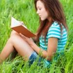 Молодая женщина сидит на траве и чтение книги — Стоковое фото #9580548
