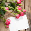 Pink roses and white card with a place for a text on a wooden ta — Stock Photo