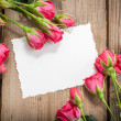 Pink roses and white card with a place for a text on a wooden ta — Stock Photo #26503445