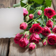 Pink roses and white card with a place for a text on a wooden ta — Stock Photo #26503453