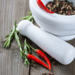Rosemary and red hot chili pepper in a mortar — Stock Photo