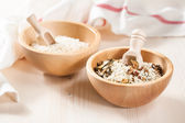 Rice in wooden bowl with ingredients for risotto — Stock Photo
