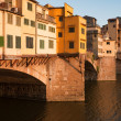 "Crowds of tourists visit Ponte Vecchio (""Old Bridge"") which is Medieval bridge over Arno River in Florence, Tuscany, Italy. — Stock Photo #29124947"