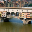 "Stock Photo: Crowds of tourists visit Ponte Vecchio (""Old Bridge"") which is Medieval bridge over Arno River in Florence, Tuscany, Italy."