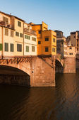 "Crowds of tourists visit the Ponte Vecchio (""Old Bridge"") which is a Medieval bridge over the Arno River in Florence, Tuscany, Italy. — Stock Photo"