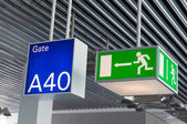 Green emergency exit sign,and blue gate sign in airport — Stock Photo