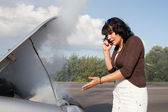 Woman near smoking car calling for help — Stock Photo