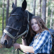 Young rider hugging her horse — Stock Photo