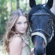 Attractive blond girl with her horse. — Stock Photo