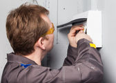 Electrician examining fuse box — Stock Photo