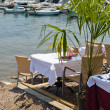 Restaurant tables on the Mediterranean Sea - Stock Photo