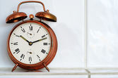 Vintage copper alarm clock on the mantelshelf — Stock Photo