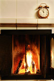 Fireplace and old-fashioned copper alarm clock on the mantelshe — Stock Photo