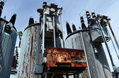 Old rusty transformer substation against the blue sky — Stock Photo